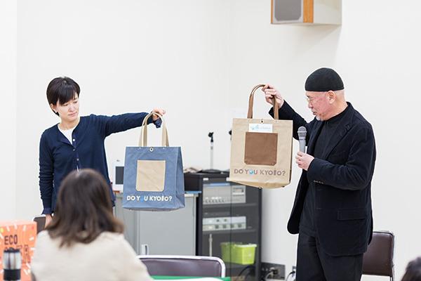 「Do You Kyoto?」は、「環境にいいことしていますか?」という意味で、世界で使われている、と京都議定書10周年記念のシンポジウムで、ドイツのメルケル首相が教えてくれたと。一澤信三郎帆布のエコバッグにも使われている。右が代表取締役社長の一澤信三郎さん