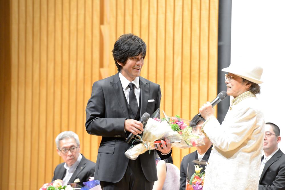主演男優賞に選ばれた俳優・佐藤浩市と、司会を務めた浜村淳
