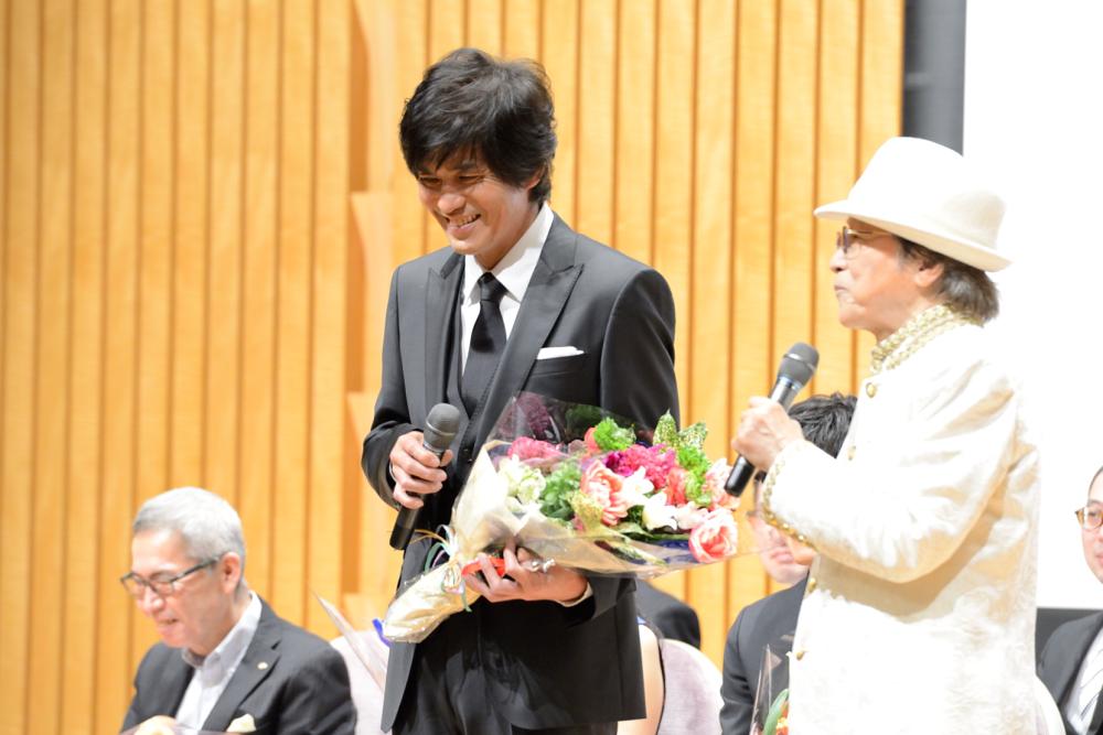 笑顔で質問に答える俳優・佐藤浩市(左)