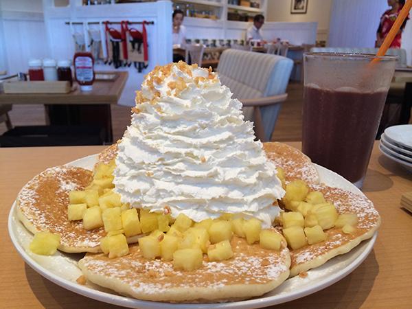 大人気のパンケーキ。真夏はパイナップル、ホイップクリームとマカデミアナッツ1,150円がおすすめ。テーブルに備え付けのグアバソースをたっぷりかけて。フローズンドリンク、アサイーバナナヨーグルトは700円