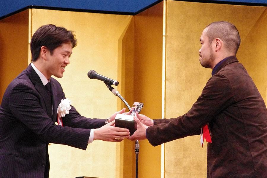 吉村洋文大阪市長から記念トロフィーを受け取る塚原悠也さん(右)