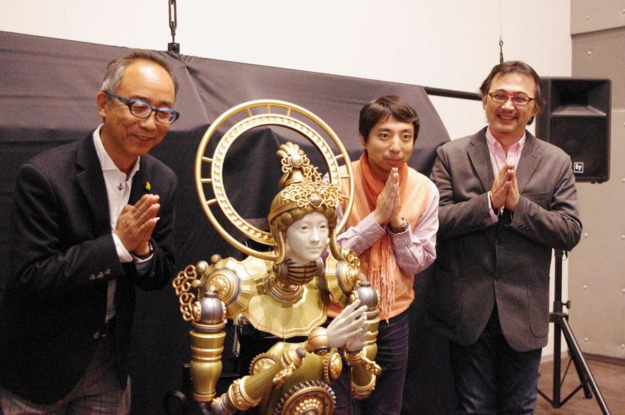 今回の仏像イメージをデザインした岸啓介さん(右から2人目)らと合掌のポーズを取るロボット