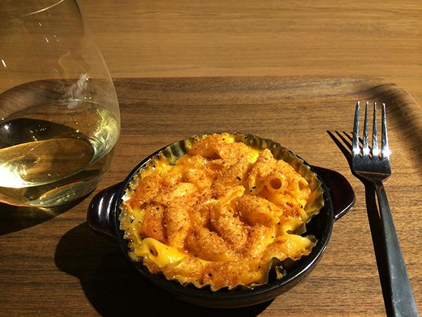 チェダーチーズがたっぷりかかり、カリッと香ばしく焼き上げたマカロニ&チーズ620円。グラスワインは、ウエスト レーン ワイナリーのヴィオニエ850円