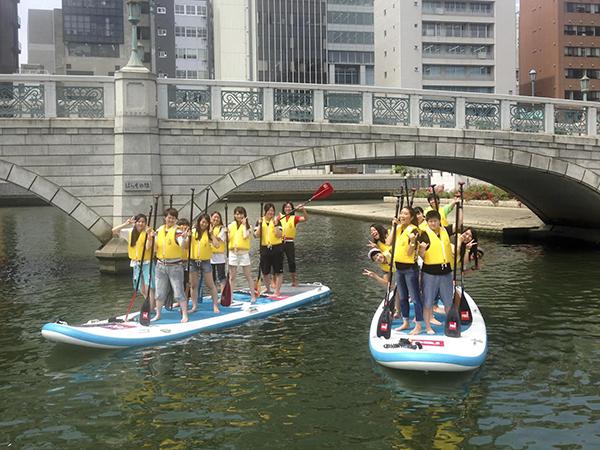 <水上でおさんぽ!>スタンドアップパドルボート(写真)やカヤック、ミニボートで安治川を親子で20分間の水上散歩。小学生の親子2名1組で申し込みを。親子1組500円