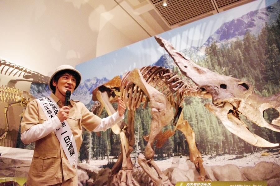 巨大な恐竜標本の前で幸せそうに解説する田中