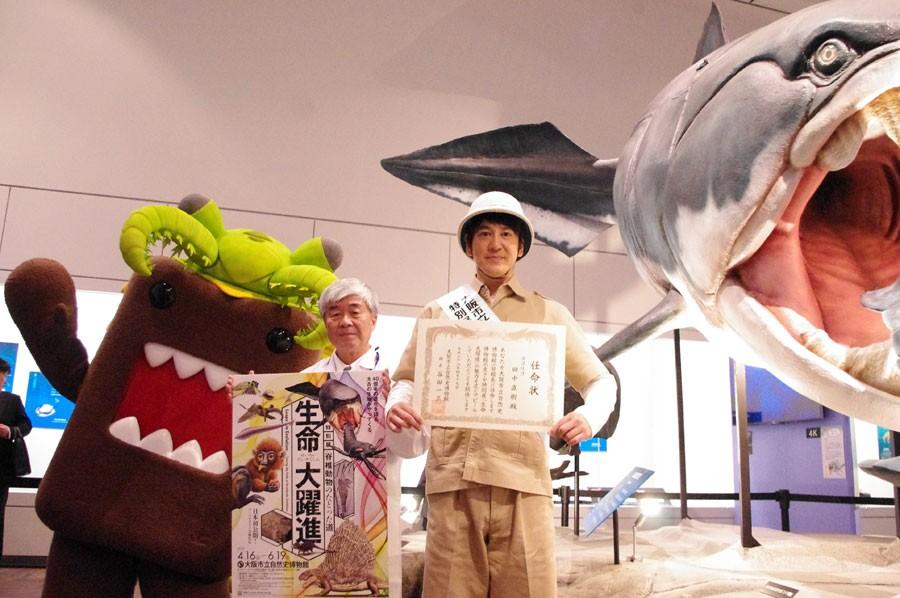 左からアノマロカリスどーもくん、谷田一三館長、田中直樹1日館長、全長6mのダンクルオステウス