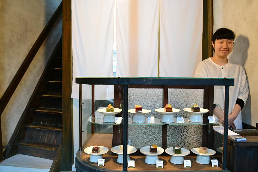 店主の西川葵さん。アンティークのショーケースをアレンジしたカウンターも特徴的