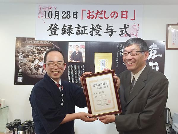 「記念日登録証」を手に、煮出し師の福本康利さん(左)と、日本記念日協会代表理事の加瀬清志さん(右)