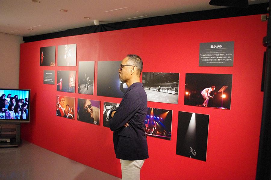 会場に展示されている写真のほぼすべてを撮ったカメラマン・梅田福夫さんの姿も