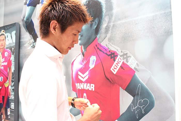 展示用パネル・ユニフォームにサインを書く柿谷曜一朗選手