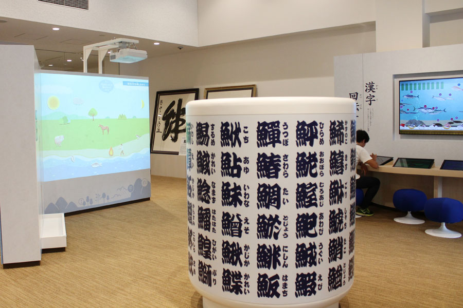 「漢字回転すし」の前にはすし屋の定番、魚へんの漢字が書かれた巨大な湯飲みが。湯のみの中から顔を出して記念撮影も