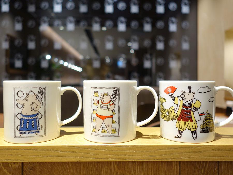 ぶーちゃんアイテムもたくさん、マグカップ各648円。Tシャツ、「秘伝のみそだれ」なども販売