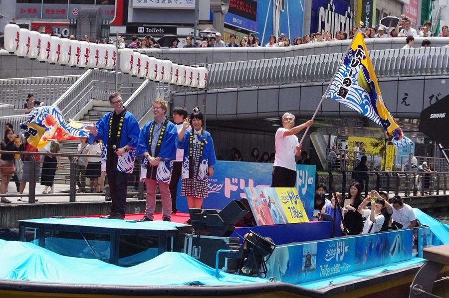 ドリーカラー(青と黄色)に染められた船に乗って登場した室井滋ら(1日/大阪・道頓堀にて)