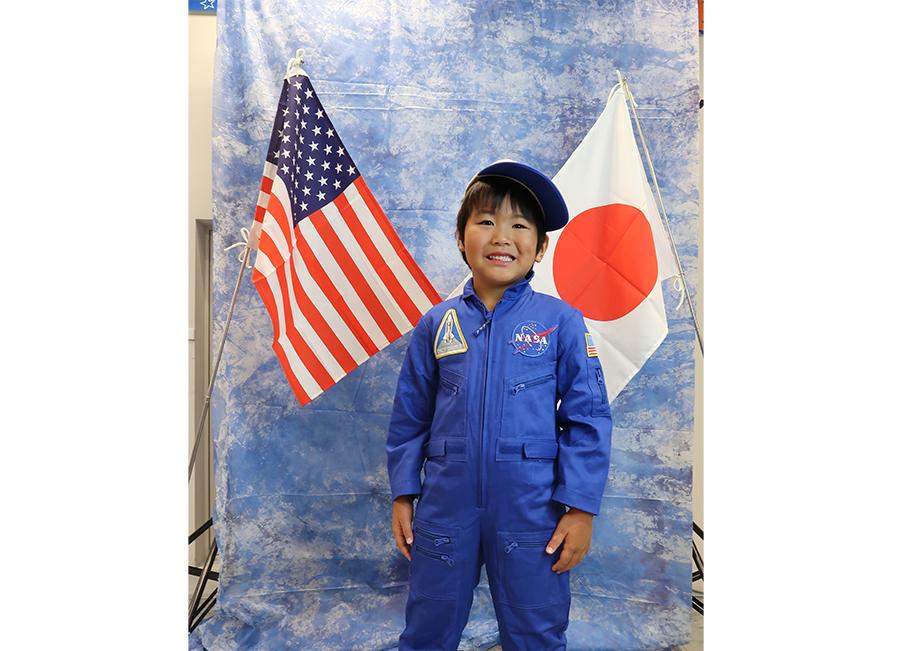 アメリカと日本の国旗をバックに、記念撮影。キャップとスーツを無料で貸し出し