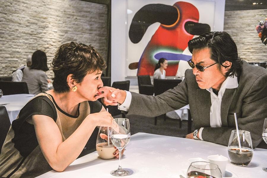 小夜子を裏であやつる、豊川演じる結婚相談所所長・柏木 © 2016「後妻業の女」製作委員会