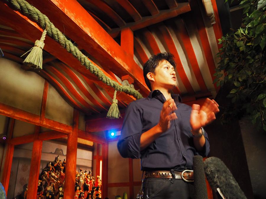 『祟 TATARI ~生き人形の呪い~』の人形たちの前で説明するホラーコンテンツ総合プロデューサーの津野さん