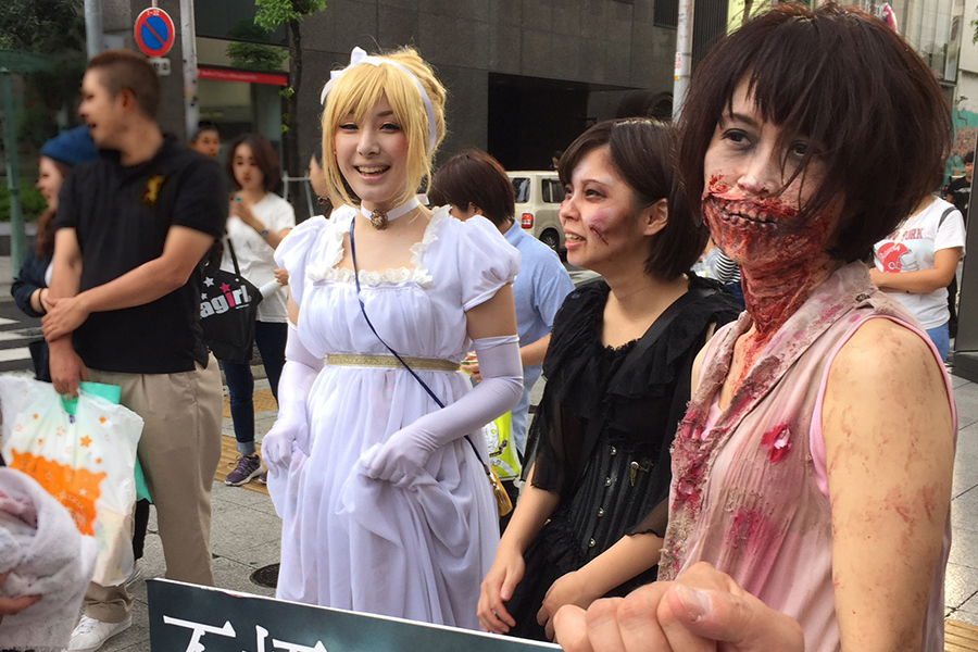 大阪の繁華街・ミナミに出現した白いドレスをまとった因幡優里さんとゾンビのコスプレイヤー(22日)