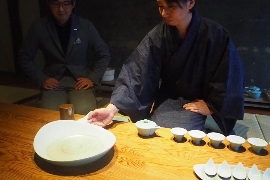 「朝日焼」による、朝日焼に施された銀彩の伝統技法とIH技術により木のカウンターに置かれた湯盤の水が沸くという茶器『銀釉』