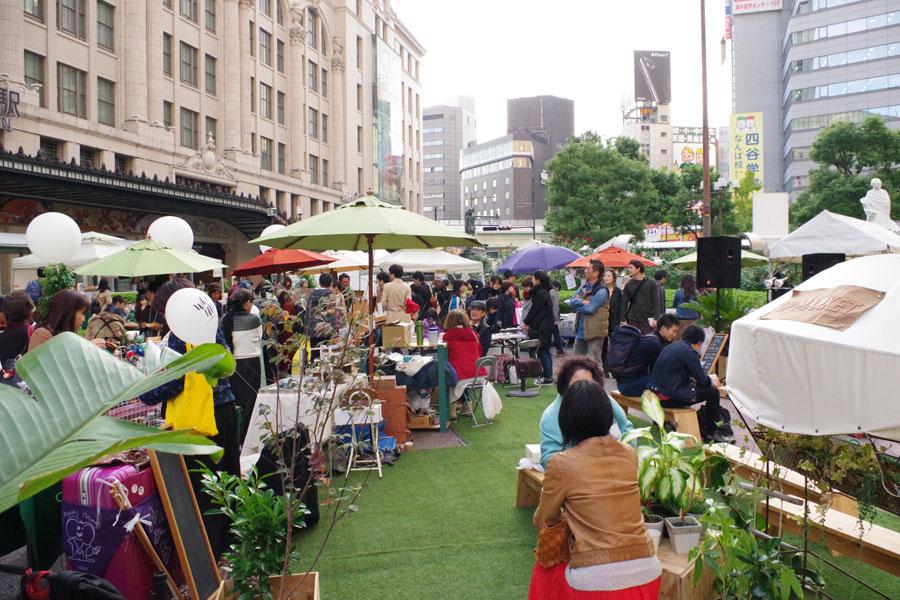 訪れた人たちは、駅前に現れたマーケットで思い思いに楽しんでいた(11日、大阪市)