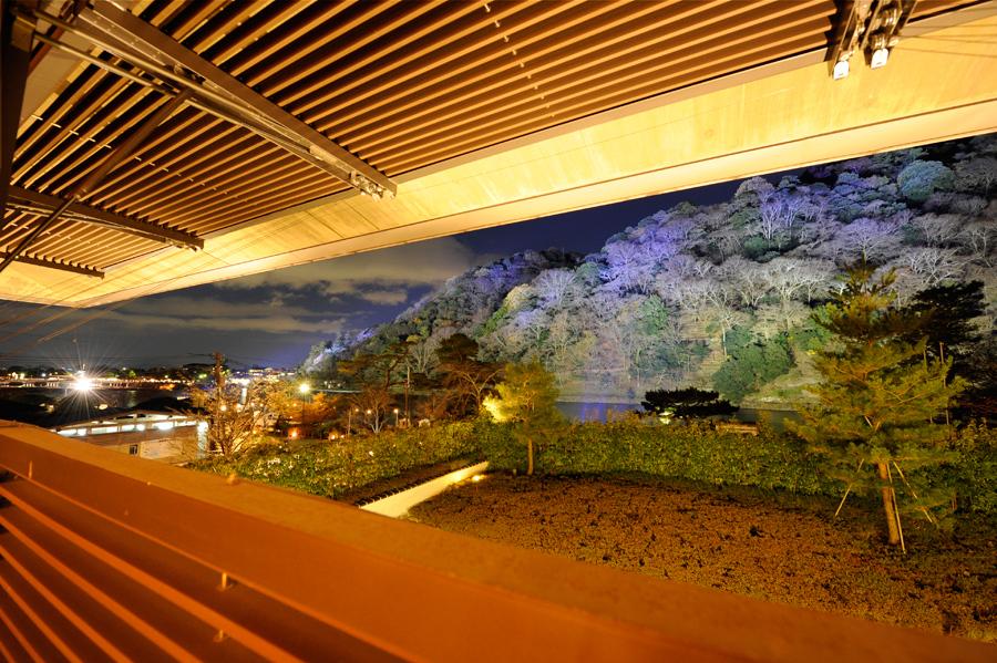 「小倉百人一首殿堂時雨殿」の暖かい室内から、嵐山の『花灯路』が一望できる