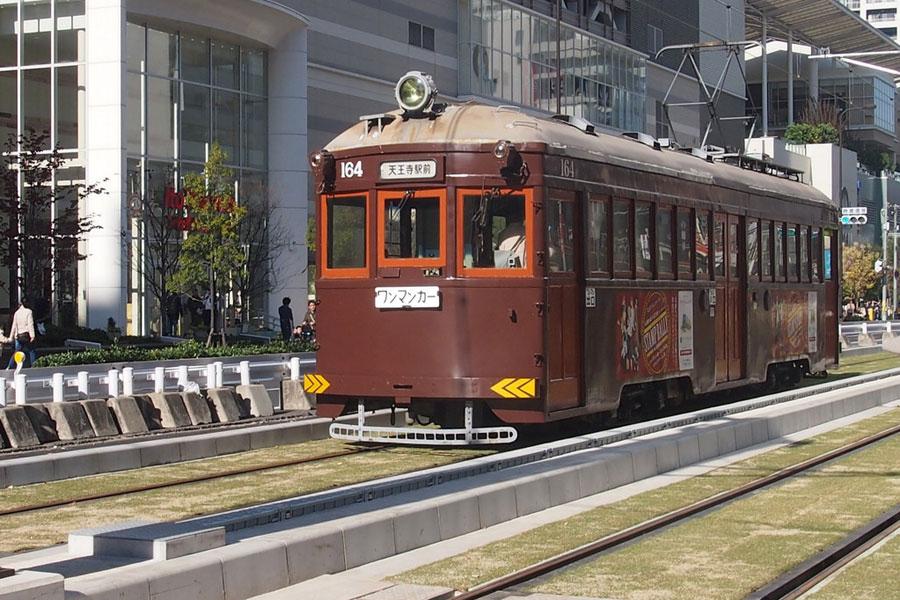 新しい芝生の軌道を走る昭和3年生まれのモ161形車両(3日、大阪市)