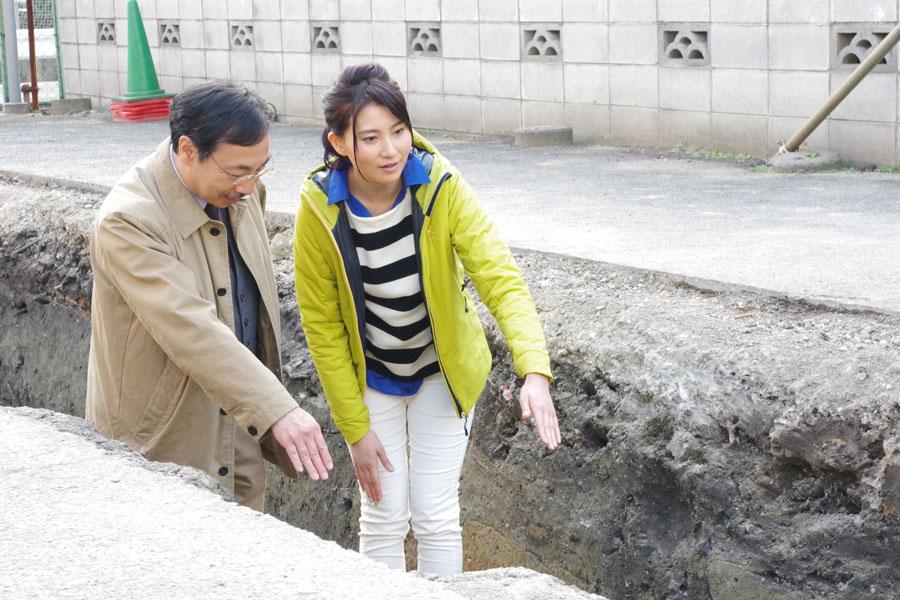 真田丸の堀の痕跡が見つかったという発掘現場で千田嘉博教授の説明を聞く井上あさひアナウンサー(9日、大阪市)