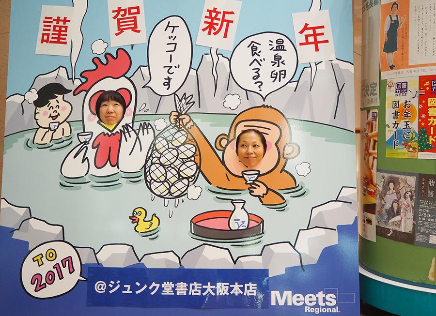 「ジュンク堂大阪本店」に設置された顔出しパネル、試しているのは雑誌担当の山川さん(左)と若崎さん(27日・ジュンク堂大阪本店)