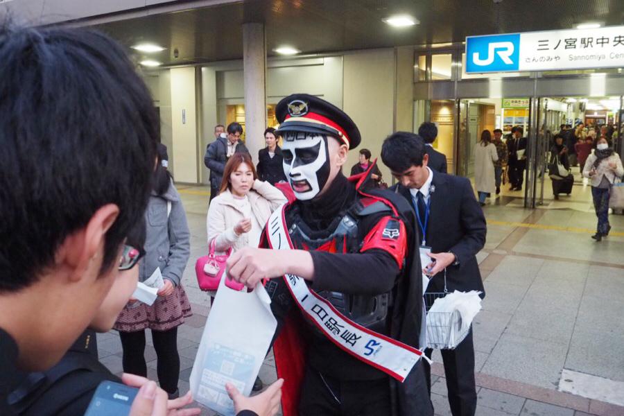 「三ノ宮駅」前でノベルティーを配布しながら呼びかける鉄拳。写真撮影にもにこやかに応じていた