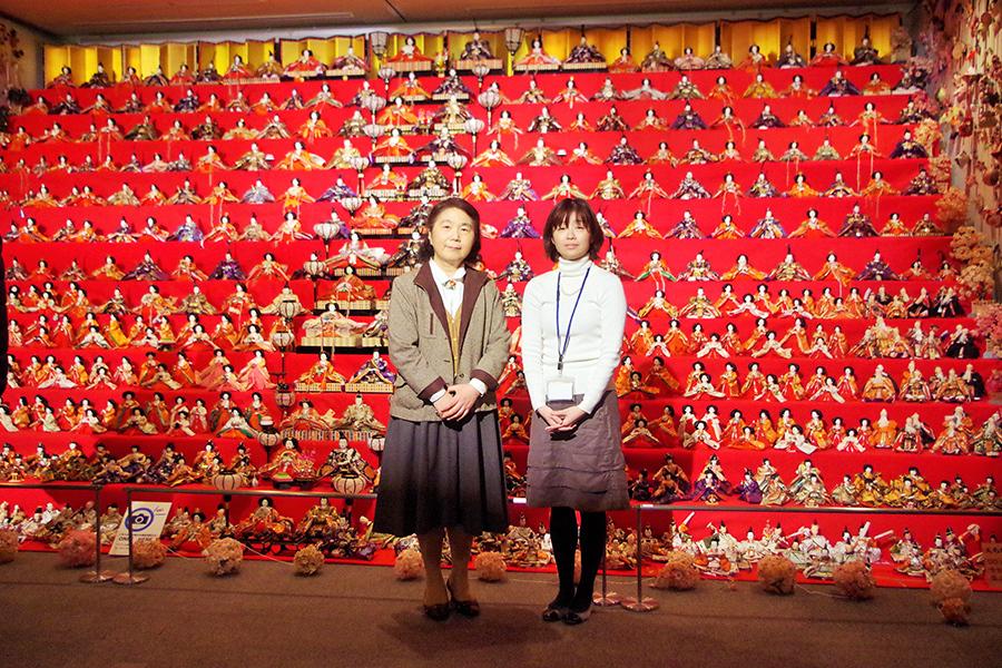 「大阪くらしの今昔館」学芸員の服部麻衣さん(右)と摂南大学外国語学部学部長・岩間香教授。学生たちと飾った大雛壇の前で
