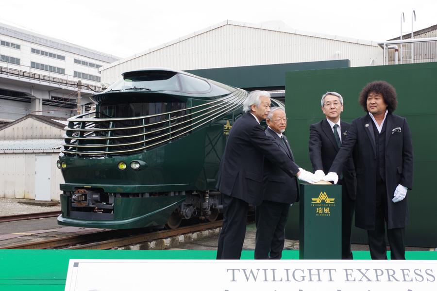 2月23日に大阪市内でおこなわれた記念式典で初お披露目されたTWILIGHT EXPRESS 瑞風と、登壇した西日本旅客鉄道の来島社長やアンバサダーでミュージシャンの葉加瀬太郎ら