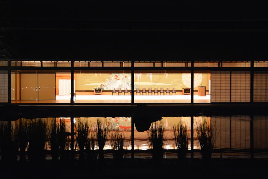 夜の京都迎賓館では、藤の間の壁面装飾の綴織りが池の水面に映りこむ