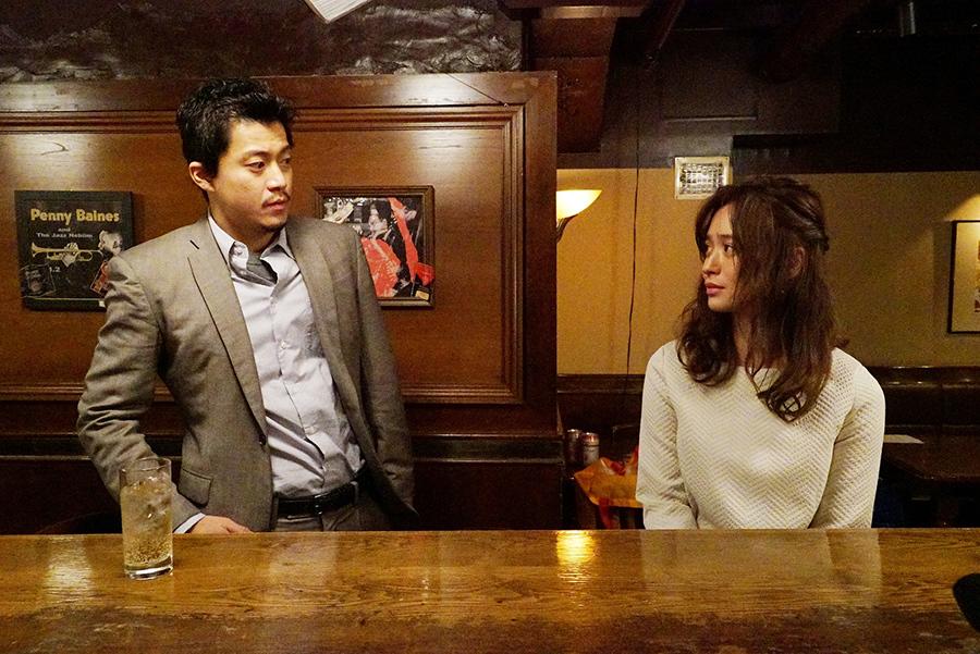 主人公・稲見(小栗旬)が行きつけのバーで大学職員・松永芳(野崎萌香)と出会うワンシーン