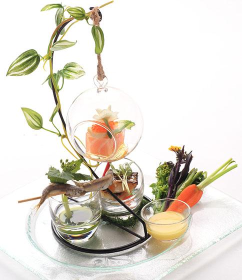 海をイメージしたガラスの器に、シーフードや旬の野菜が盛られた、見た目も美しいアミューズ