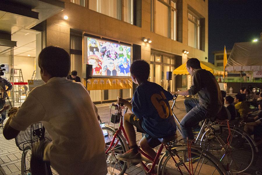 自転車をこがないと映画が止まってしまう、自転車発電の上映会の様子