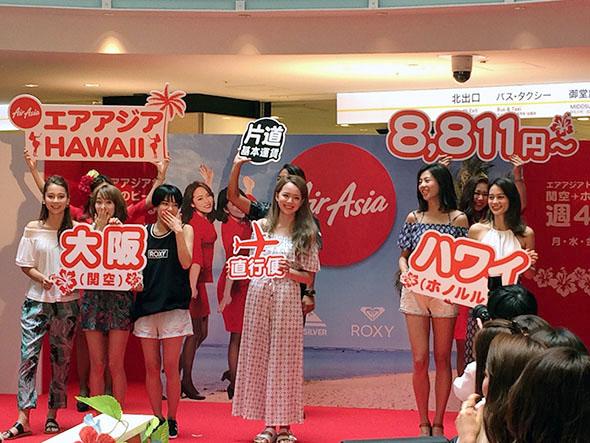 エアアジアのキャビンクルーと一緒にフリップボードを掲げるゲストたち