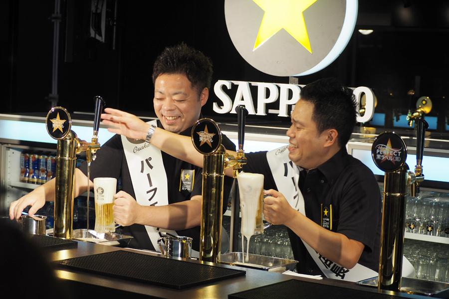 記念すべき1杯目をサーブするも失敗する西澤(左)