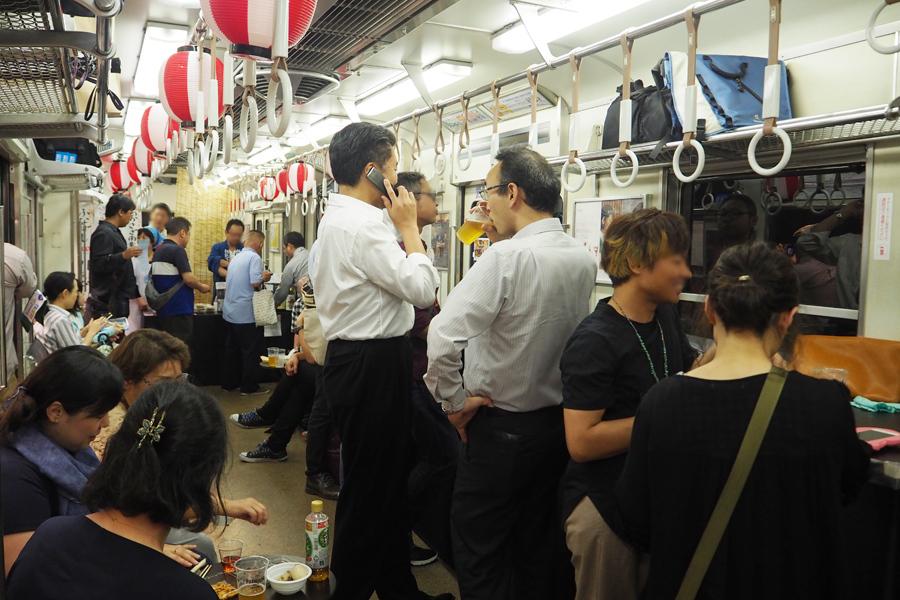 んで飲む人、網棚に荷物を置いて飲食する人など電車内酒場らしい光景があちこちで見られた