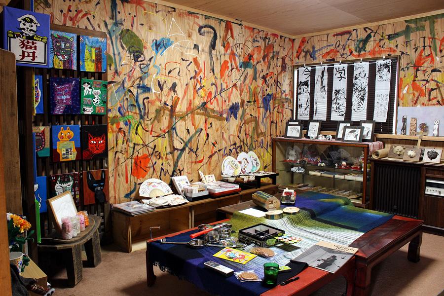 「うと・うと」店内。壁一面のペインティング、奥の墨絵作品等は、現代アート作家・堀尾貞治氏の作品