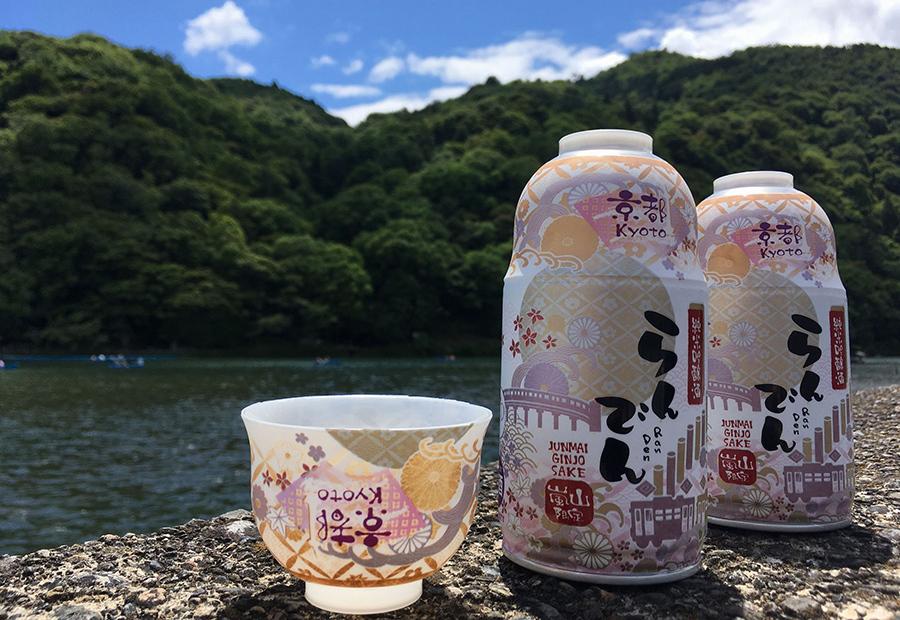 お猪口付きの缶に渡月橋や嵐山車両がデザインされた純米吟醸酒「らんでん」
