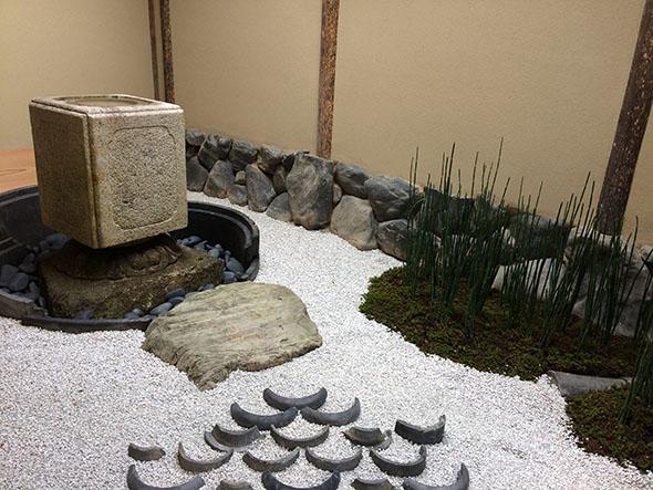前庭は表千家の組み方を取り入れて。白砂利にあしらった瓦は、スターバックスのシンボル、セイレンの鱗と古典文様、青海波をイメージしている