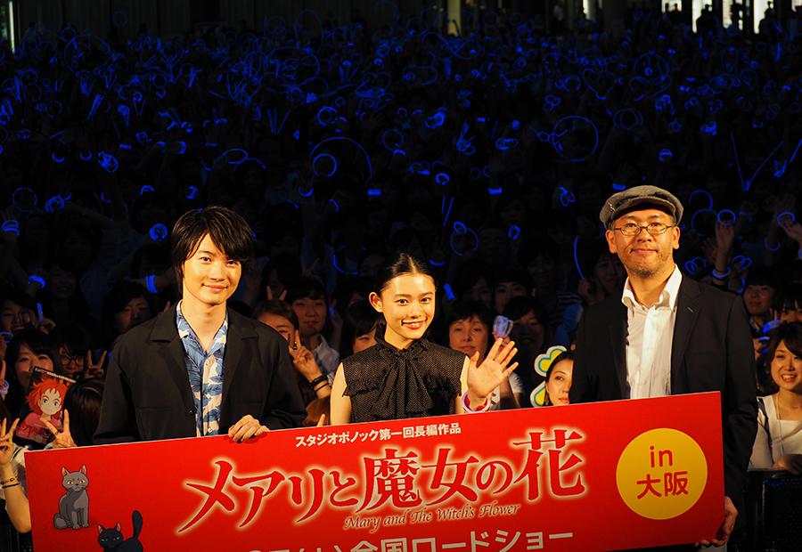 観客たちは、映画に登場する不思議な花「夜行飛行」をイメージした青いサイリウムを手に記念撮影(28日・大阪市内)