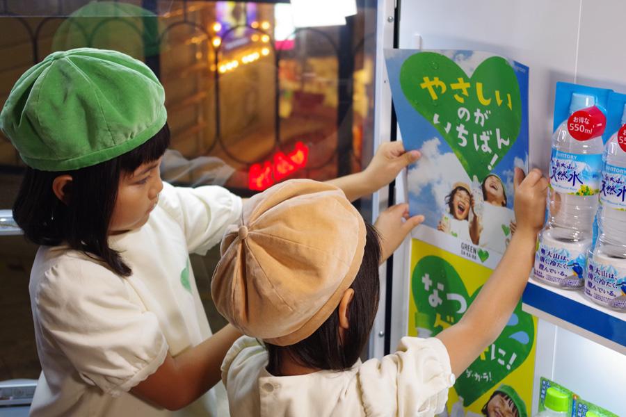 自販機のポスターを自分たちが写るGREEN DA・KA・RAに張り替える2人