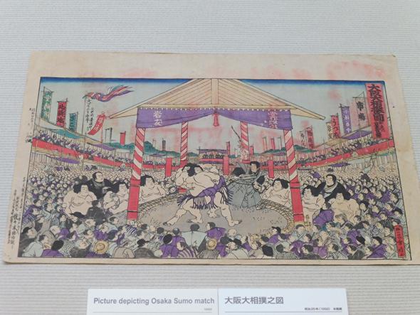 大阪大相撲之図 明治25年(1892) 大阪歴史博物館蔵 観客席の上部に「うつぼ(靭)」、「堂嶋浜」、「ざこば(雑喉場)」など市場があった土地の幟(のぼり)があり、当時の大阪相撲と市場の密接な関係がうかがえる