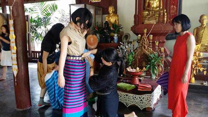伝統舞踊のレッスンで、民族衣装を着付けてもらう