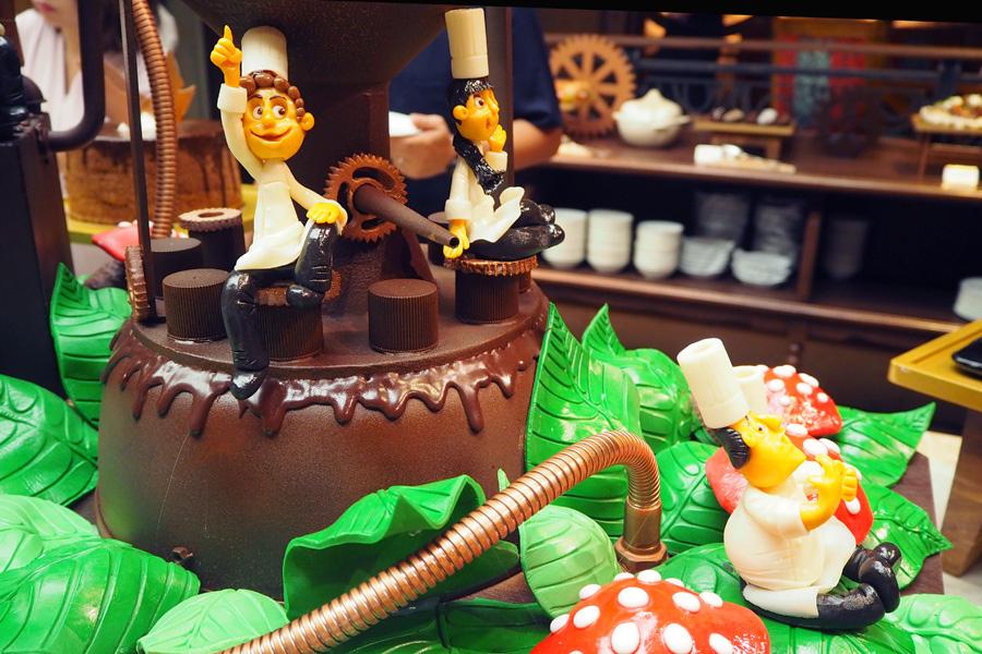 「チョコレートの工場」をテーマに、パイプやシリンダーなどをチョコレートでコーティングした装飾が施された会場