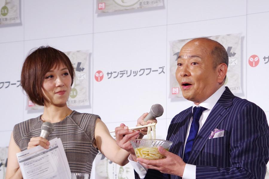 「うまいっ」と試食の冷やしすだちうどんを食べる山本アナ。今回、ラジオで流れるCMソングも作曲し、自ら歌っている