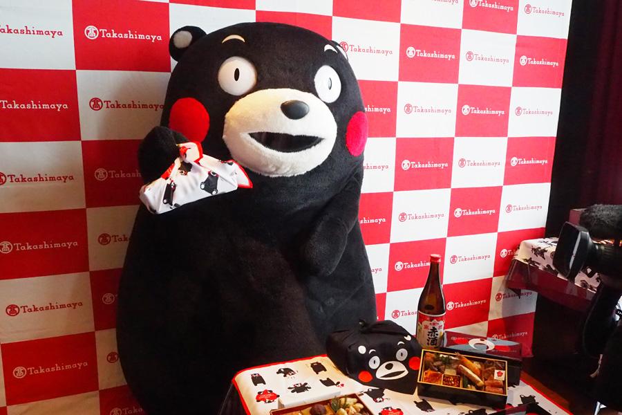 「熊本おせち」を紹介するくまモン(持っているのは、和・洋一段16200円)