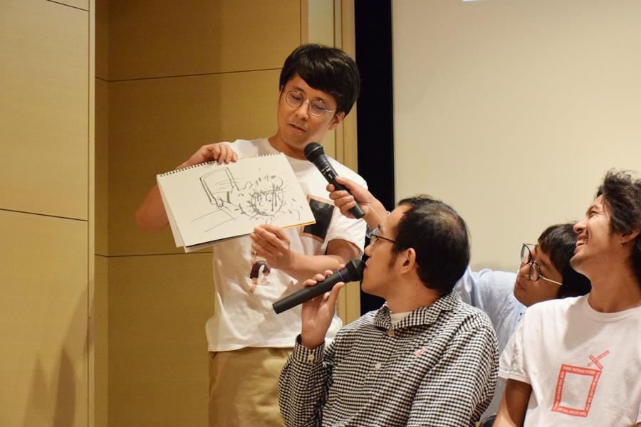 スケッチブックにイラストを描き、見どころをプレゼンする角田