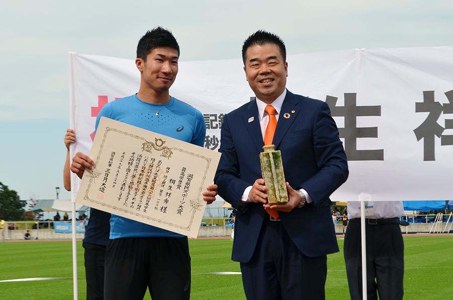 桐生選手に贈呈された賞状と信楽焼の記念品(右は三日月知事、24日・東近江市)