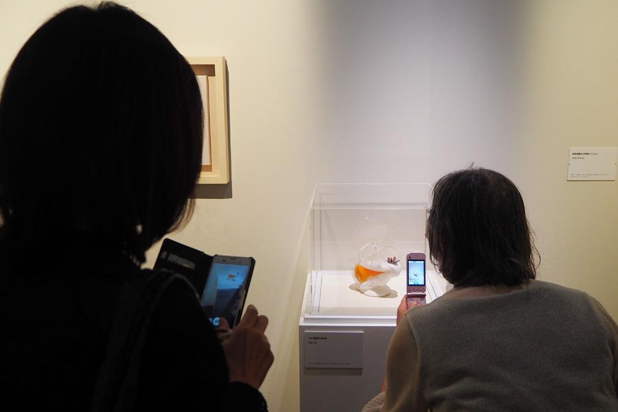 携帯を片手に作品を観賞する人々